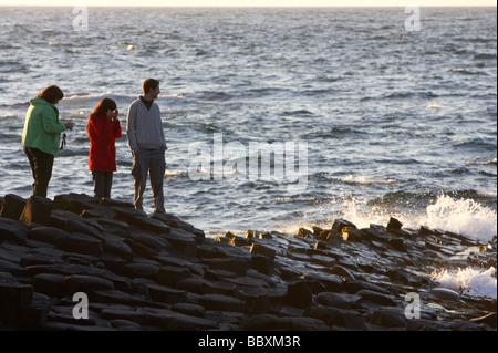 tourists watch the waves on the giants causeway county antrim coast northern ireland uk europe - Stock Photo