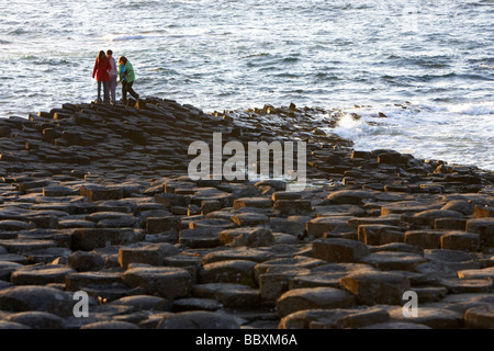 tourists walk over the giants causeway county antrim coast northern ireland uk europe - Stock Photo