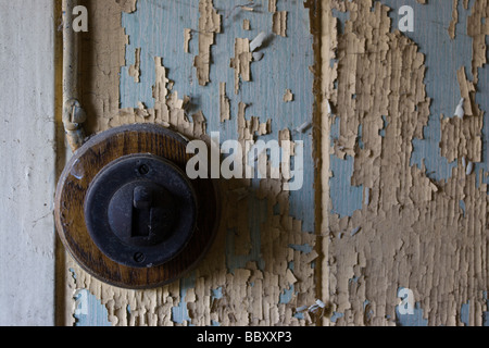 Light switch on wall with pealing paint - Stock Photo
