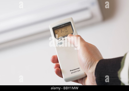 Hand using remote control of a reverse cycle air conditioner heat pump seen in background - Stock Photo