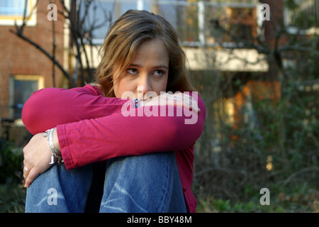 Sad teenage girl distressed, depressed teen thinking in front of apartment building - Stock Photo