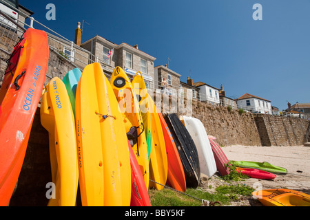 Canoes leaned up agsainst the sea wall in mousehole in Cornwall UK - Stock Photo