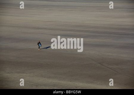 a lone surfer walks across the beach carrying his board to get to the sea - Stock Photo