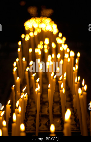 Votive candles burning in a church - Stock Photo