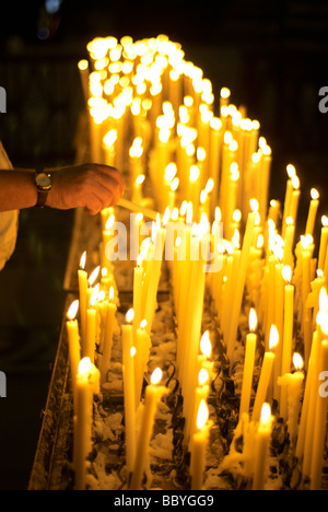 Man lighting votive candle in church - Stock Photo