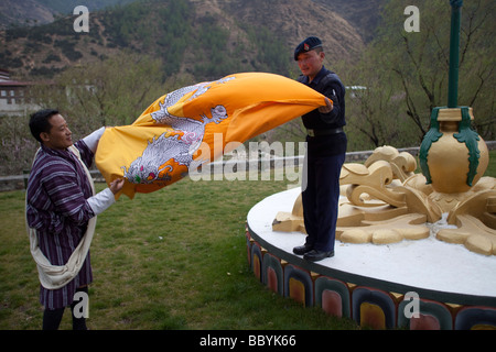 Bhutanese soldier guard folding up Bhutan National Flag at the King's Palace, Thimphu. Horizontal View