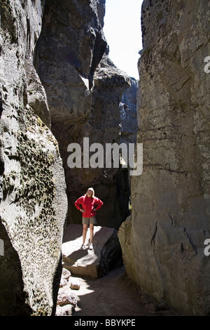 A hiker in Crack In The Ground in Christmas Valley Oregon - Stock Photo