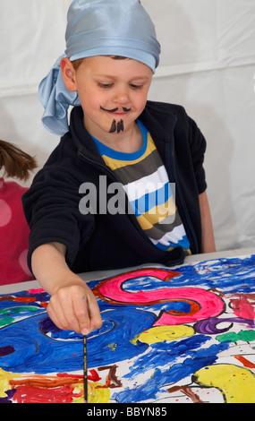 young boy wearing fancy dress pirate costume painting a mural - Stock Photo