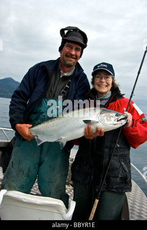 Female angler wearing resort baseball cap with fishing guide holding a freshly landed Haida Gwaii chinook salmon - Stock Photo