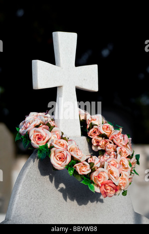 A cross on a gravestone adorned with a wreath of flowers