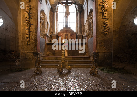 Altar in old church ossuary with human skulls and bones on walls Kutna Hora Czech Republic - Stock Photo
