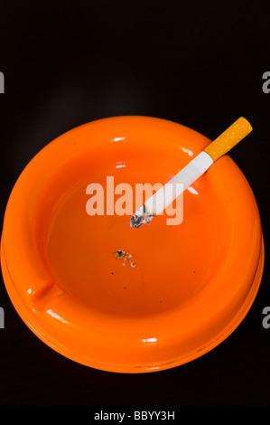 High angle view of cigarette in orange ashtray - Stock Photo