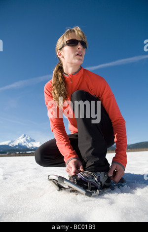 Young woman straps on snowshoes with Mt. Hood, Oregon in background. - Stock Photo
