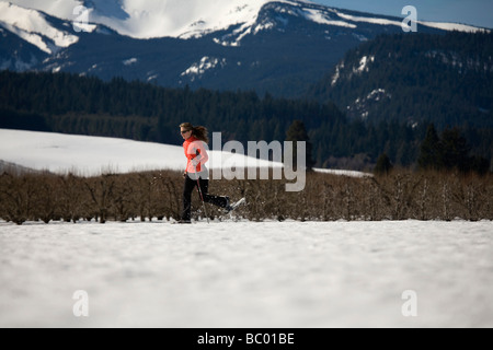 Young woman runs through snow with snowshoes near Mt. Hood, Oregon. - Stock Photo
