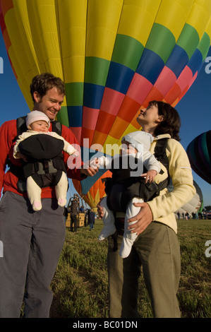 A family with twin babies watches hot air balloons launch during a festival. - Stock Photo