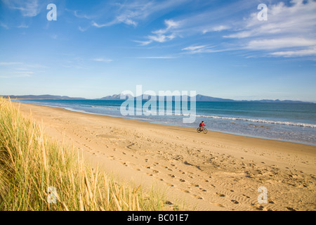 A woman enjoying a bike ride on Nine Mile Beach on the east coast of Tasmania, Australia. - Stock Photo
