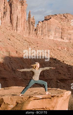 Woman in yoga pose on sandstone rock below sandstone towers, Moab, Utah. - Stock Photo