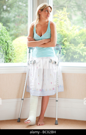 Woman at home with leg in plaster - Stock Photo