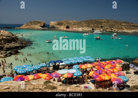 Tourists sunbathing and swimming in the Blue Lagoon, Comino, Malta. - Stock Photo
