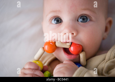 three month old baby girl grasping and mouthing a teething ring made of wooden beads, chewing on toy - Stock Photo