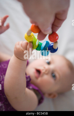 three month old baby girl reaching for a wooden teething toy - Stock Photo