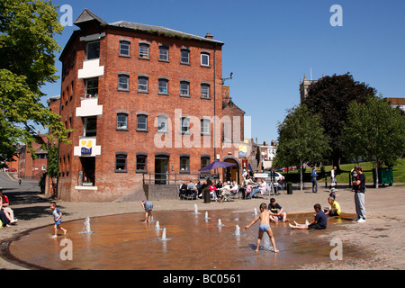 children playing in the quayhead square water fountain near st andrews gardens worcester uk - Stock Photo