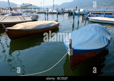 Covered boats moored in the marina at Iseo Brescia Lombardy Italy protected from the weather by tarpaulin - Stock Photo