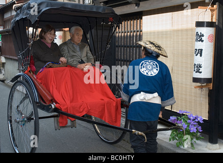 An elderly couple takes a leisurely ride in a jinrikisha along Sannomachi street in the old district of Takayama - Stock Photo