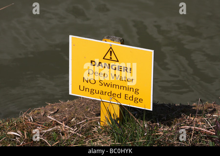 Danger warning sign for deep water and unguarded edge. - Stock Photo