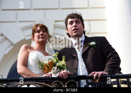 A newly married couple stand on a balcony and have their picture taken from below - Stock Photo