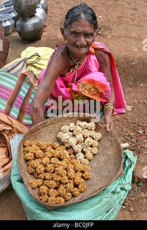 Indian Woman Of The Paroja Tribe Selling Sweet Pastries, Orissa - Stock Photo