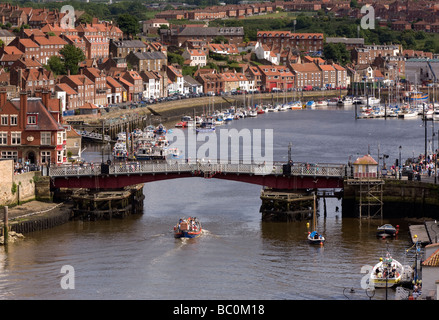 A tourist boat goes under the swing bridge in Whitby Harbour - Stock Photo