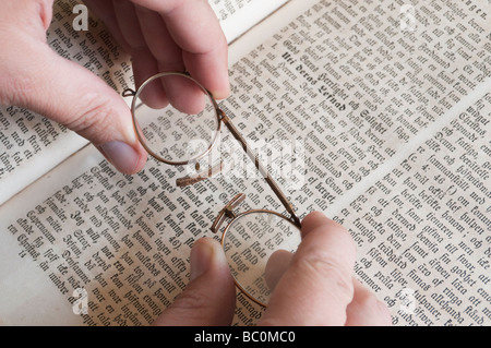 Hands holding a pair of pince-nez eye-glasses over Swedish bible. - Stock Photo