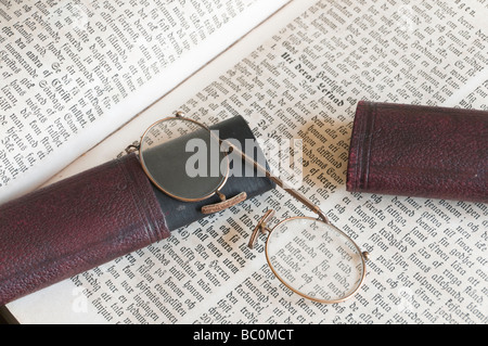 A pair of old pince-nez eye-glasses with case on old Swedish bible. - Stock Photo