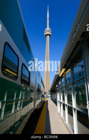 CN Tower between GO train and Union Station Toronto with blue sky in the morning - Stock Photo