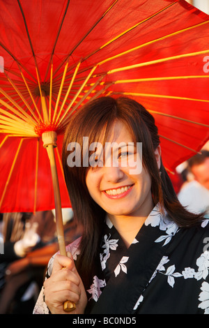 Young girl wearing a black & white Kimono with a red japanese paper umbrella on the Japanese Day in Düsseldorf 2009 - Stock Photo