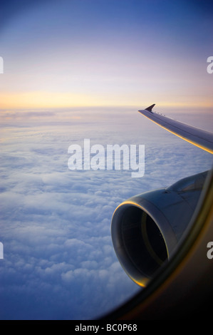 Jet Engine And Wing During Flight At Sunset - Stock Photo