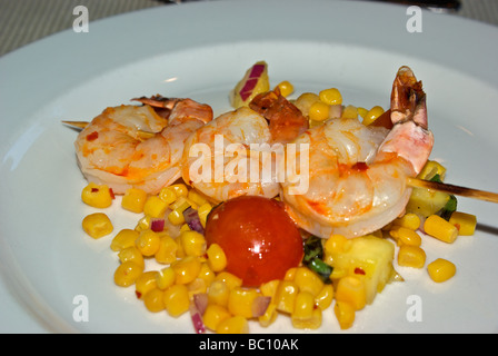 Three grilled prawns on a skewer over a hot red pepper spiced corn with pineapple tomato salsa - Stock Photo
