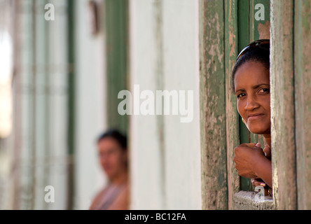 Cuban woman peering from a hatch in the door to her home. Trinidad, Cuba. Trinidad is a World heritage site - Stock Photo