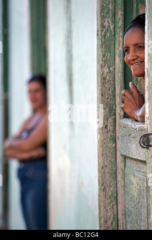Smiling Cuban woman peering from a hatch in the door to her home. Trinidad, Cuba. Trinidad is a World heritage site - Stock Photo