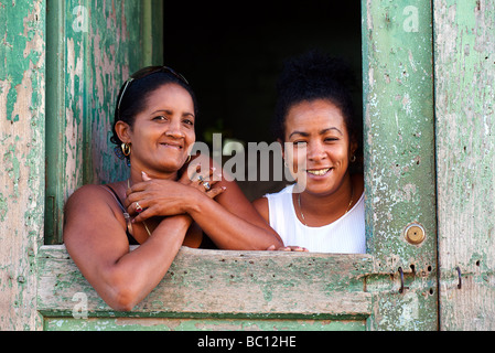 Cuban women greeting from a hatch in the door to their home. Trinidad, Cuba. Trinidad is a World heritage site - Stock Photo