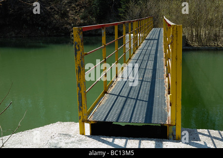 Steel footbridge over river channel - Stock Photo