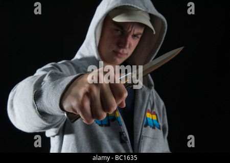 Threatening youth in hoody waving knife - Stock Photo