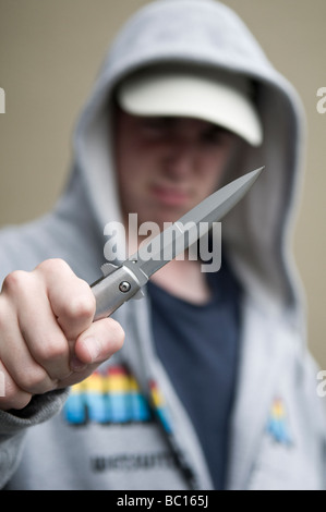 Youth in hoody brandishing flick knife - Stock Photo