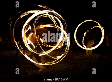 Fire Dancers creating patterns in the night during the summer solstice at Avebury in Wiltshire - Stock Photo