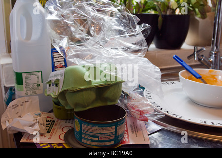 mess in the kitchen with rubbish piling up on kitchen worktop waiting to be recycled - Stock Photo