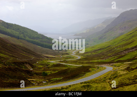 Empty road winding through a deserted valley in the highlands of Scotland - Stock Photo