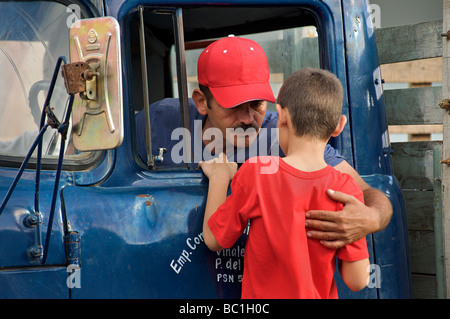 Cuban truck driver embracing his son at the window to his cab. Viñales, Pinar del Rio, Cuba - Stock Photo