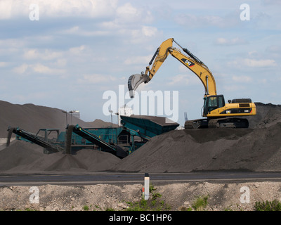 Large piles of metal ore with caterpillar excavator in the Rotterdam port area Zuid Holland the Netherlands - Stock Photo