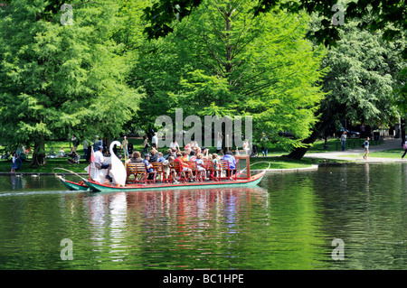 A Swan boat  ride in the Boston Public Garden's lagoon located adjacent to Boston Common, Boston MA - Stock Photo